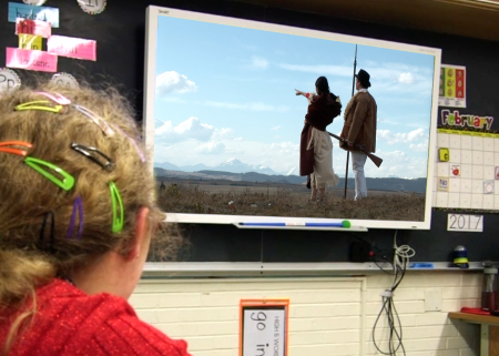 Young girl watches Sacagawea video on screen in front of blackboard