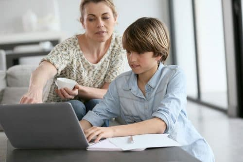Parent instructing child on laptop while sitting at a coffee table